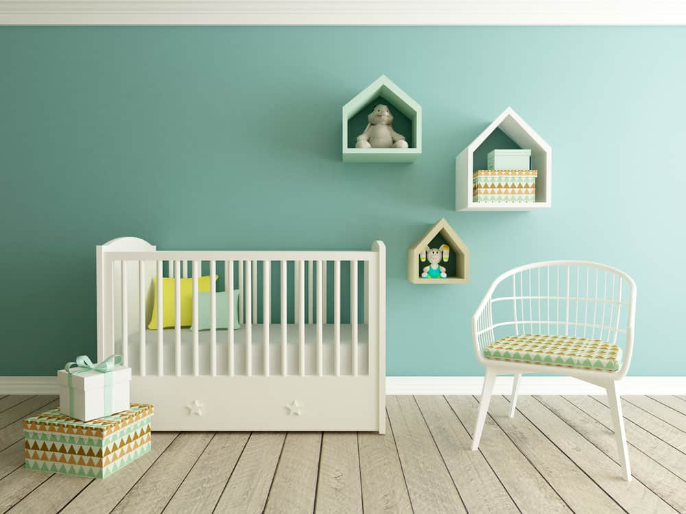baby nursery room with white crib, green walls and gender neutral decor