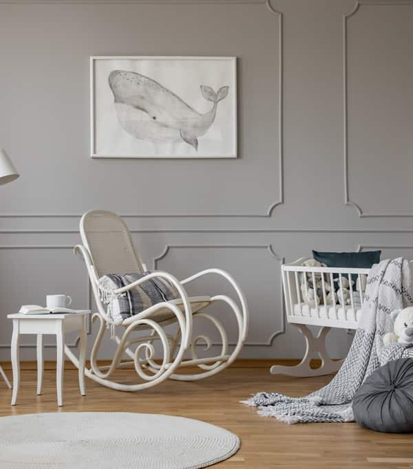 White rocking chair with pillow in the middle of cozy baby room interior with wooden cradle, industrial white lamp and poster in frame on the empty grey wall