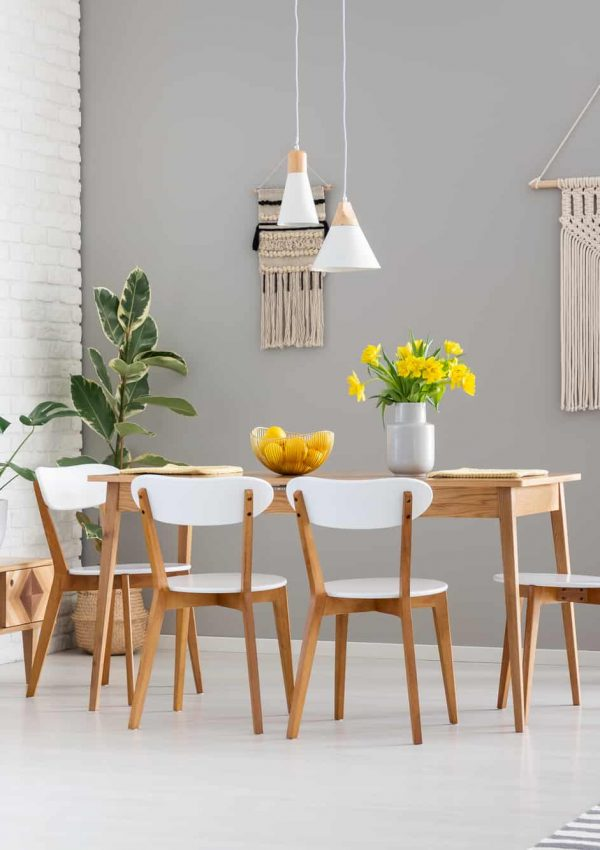 White chairs at wooden table with yellow flowers in dining room interior with plants.
